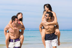 Two Couple On Beach Summer Vacation, Young People Happy Smiling, Man Carry Woman Sea Ocean Stock Photo