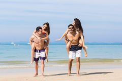 Two Couple On Beach Summer Vacation, Young People Happy Smiling, Man Carry Woman Sea Ocean Royalty Free Stock Photos