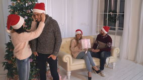 Two couple in love at home wearing in santa hat. Young people kissing near christmas tree. Handsome man giving gift adult caucasian woman on new year party stock footage
