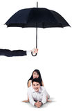 Two couple lying in studio under umbrella Royalty Free Stock Photography