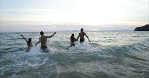 Two Couple Running In Sea Water Making Splash Holding Hands, Group Of Friends On Beach At Sunset Having Fun stock video footage