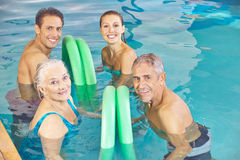 Two couples in aqua fitness class in swimming pool. Two happy couples in aqua fitness class in a swimming pool with swim noodles Stock Photos