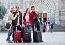 Two couples with baggage sightseeing and smiling Royalty Free Stock Photography
