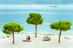 Two couples on the beach of Limone sul Garda, Italy. Two couples of different ages sitting on the beach of Limone sul Garda, Italy Royalty Free Stock Image