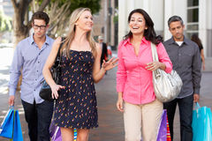 Two Couples With Bored Men Carrying Partners Bags Stock Image