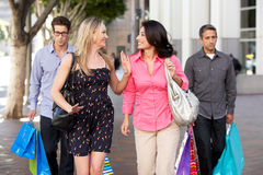 Two Couples With Bored Men Carrying Partners Bags Royalty Free Stock Photo