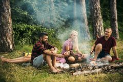 Two couples camping in woods. Men cooking sausages on campfire. Tired brunette lying on blond girls lap stock photo