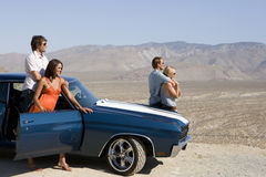 Two couples by car in desert, looking at view, side view Stock Photos