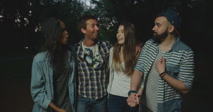 Two couples of the cheerful hipster friends are talking, laughing during their evening walk in the park. stock footage