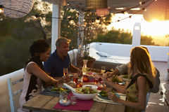Two couples eating dinner at sunset on a rooftop terrace Stock Photos
