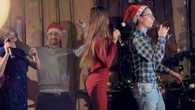 Two couples enjoy Christmas Eve party dancing and singing together. Two friends in Santa hats join two women for singing and dancing at a Christmas party stock video footage