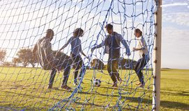 Two couples enjoy a game of football, seen through goal net Royalty Free Stock Photo