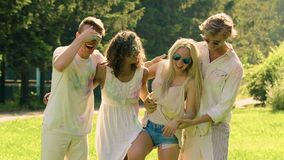 Two couples enjoying holidays and smudging colorful powder at Holi festival. Stock footage stock footage