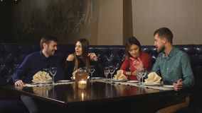 Two Couples Enjoying Meal In Restaurant Together stock video footage
