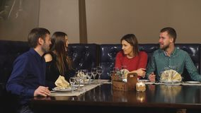 Two Couples Enjoying Meal In Restaurant Together. Two couples by eating in a restaurant stock video footage