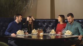 Two couples enjoying meal together. Couple toast with red wine - Scene from a restaurant stock footage