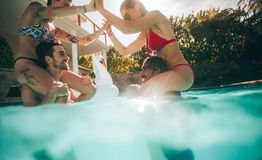 Couples playing and enjoying in a swimming pool. Two couples enjoying in swimming pool. Women sitting on shoulders of their boyfriends at pool party Royalty Free Stock Photo