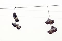 Two couples fragmentary sneakers on wires Royalty Free Stock Photos