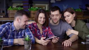 Two couples of friends who are happy with a pleasant time together make photos for memory on a mobile phone in a stock footage