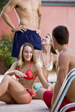 Two couples hanging out by pool Royalty Free Stock Photo