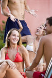 Two couples hanging out by pool Stock Photography
