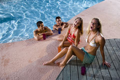 Two couples hanging out on swimming pool deck. Young adult friends laughing together by swimming pool Royalty Free Stock Photos