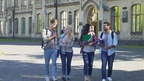 Two couples of happy students walking near college and talking, carefree youth. Stock footage stock footage