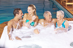 Two couples having fun in whirlpool. With foam bubble bath Royalty Free Stock Photo