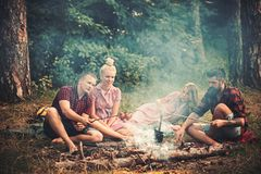 Two couples having picnic in woods. Bearded man and his best friend cooking sausages over fire. Young hikers around royalty free stock photo