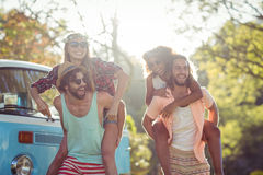 Two couples having piggy ride in park Stock Image