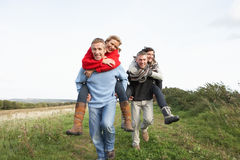 Two Couples Having Piggyback Ride Stock Photo
