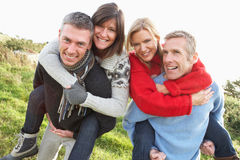 Two Couples Having Piggyback Ride In Autumn. Landscape Royalty Free Stock Photo