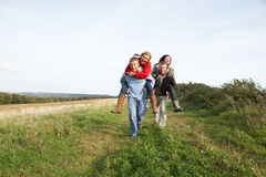 Two Couples Having Piggyback Ride In Autumn Royalty Free Stock Photos