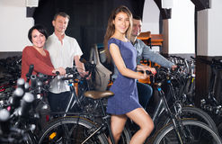 Two couples hiring bicycles. Happy young and mature couples hiring bicycles ot rental store Royalty Free Stock Images