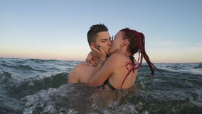 Two couples in love in the sea man and woman kissing with passion stock video