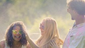 Two couples in love spraying colorful paint at each other during Holi festival. Stock footage stock video