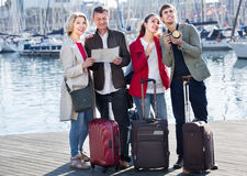 Two couples with luggage search for sights on map Stock Photos