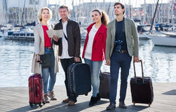 Two couples with luggage search for sights on map Royalty Free Stock Photo