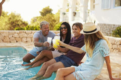 Two couples make a toast with legs dipping in swimming pool Royalty Free Stock Image