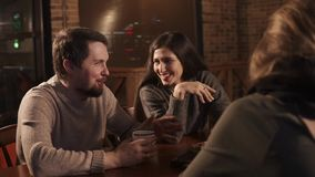 Group of friends telling stories and having fun. Two couples meet together in a restaurant and sitting at the table. They are laughing and talking stock video