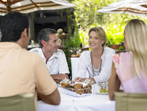 Two Couples At Outdoor Table Chatting Royalty Free Stock Image