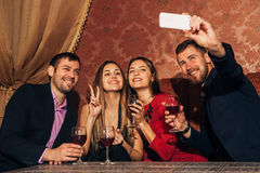 Two couples at the party take a selfie with glasses Royalty Free Stock Image