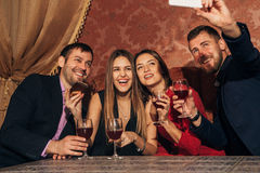 Two couples at the party take a selfie with glasses Royalty Free Stock Images