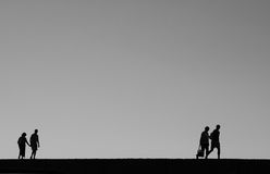 Two couples at the quay. Back lighting. B&W image. Space for text Royalty Free Stock Images