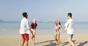 Two couples running on beach to water woman hold man hands happy cheerful people tourists on vacation. Slow motion stock video