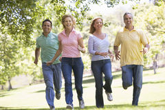 Two couples running outdoors smiling Royalty Free Stock Photo