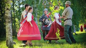 Two couples in Russian clothes dancing traditional dances on the field by the accordion music. Mid shot stock video footage