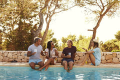 Two couples sit at poolside talking, front view Royalty Free Stock Photos