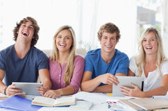 Two couples sit together and work with the help of tablet pc's Stock Images