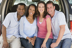 Two couples sitting in back of van smiling Stock Photography